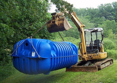 photo of septic system being installed blue tank heavy equipment